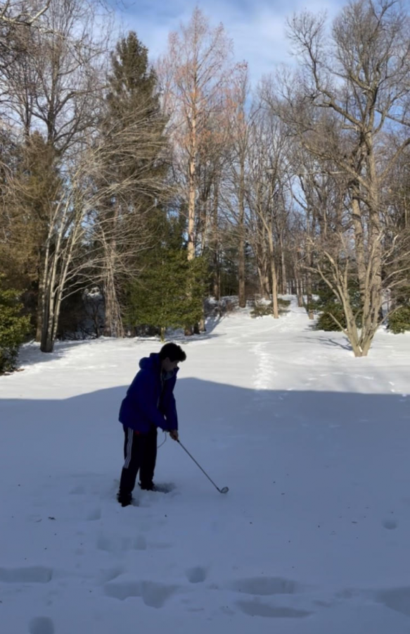 Matthew Wang '21 hits some golf balls in his backyard on February 5, 2021.